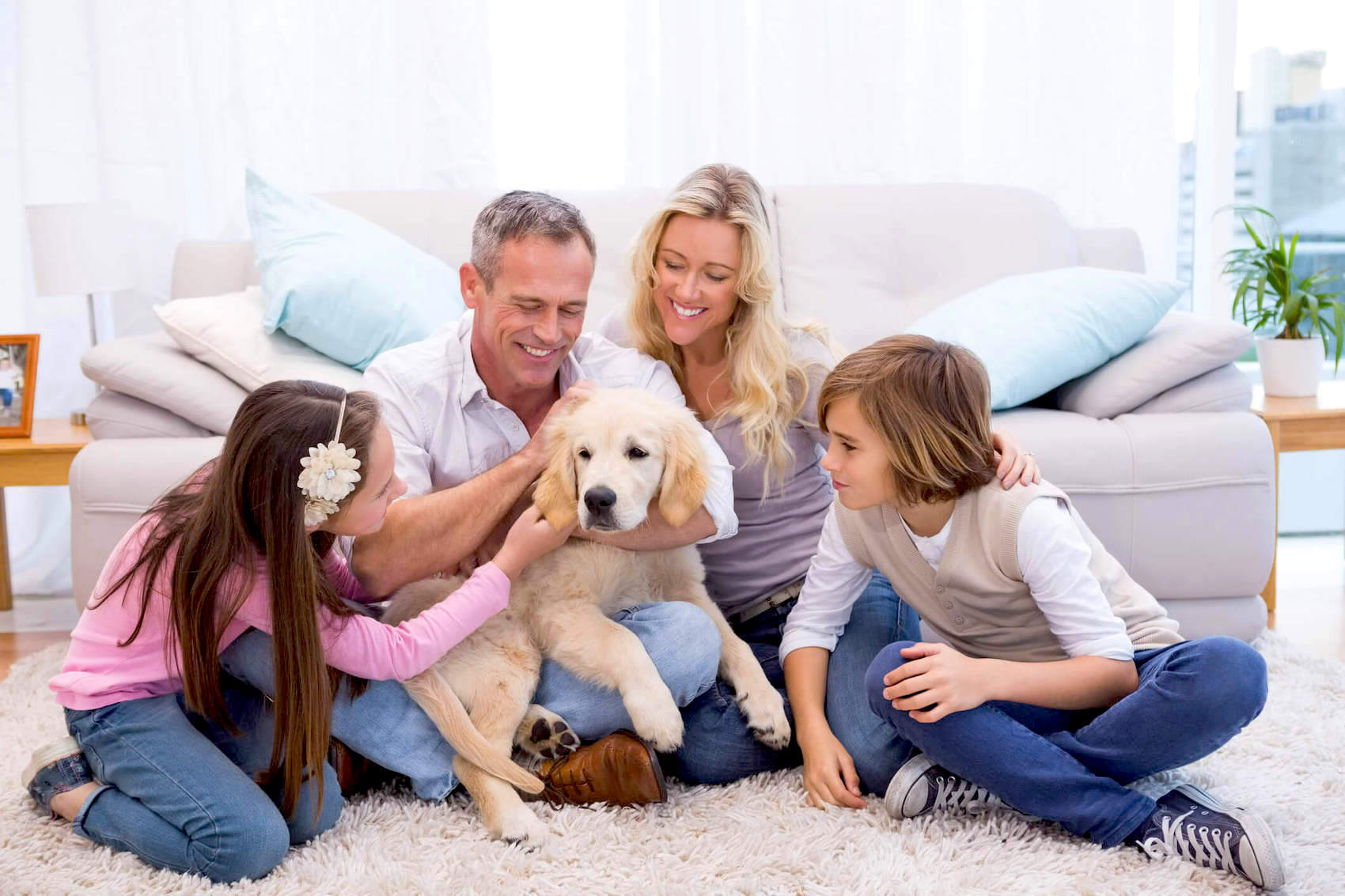 A family sitting around a golden retriever puppy in an air conditioned room.