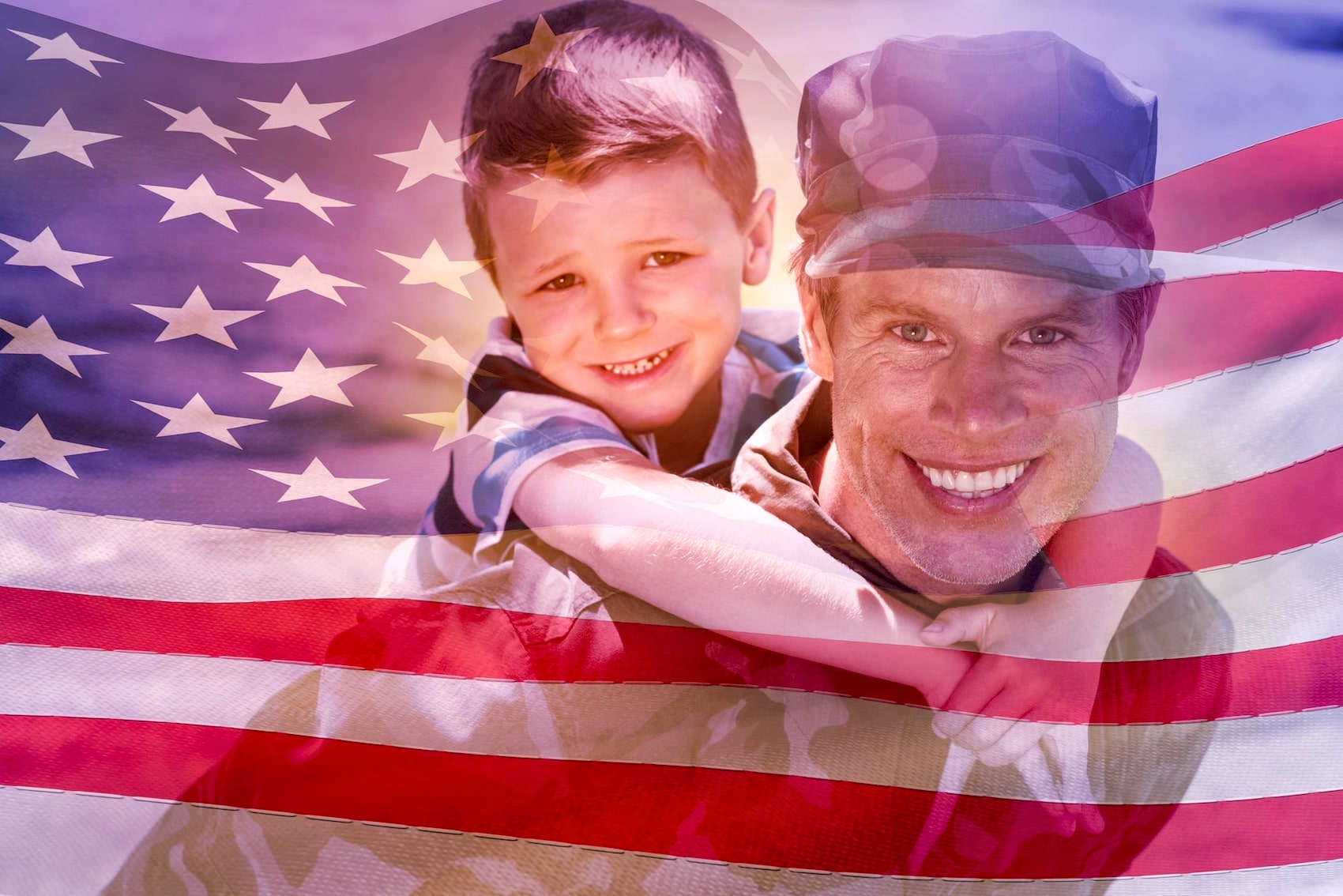 US Soldier carrying his son on his back with an American Flag in the background.